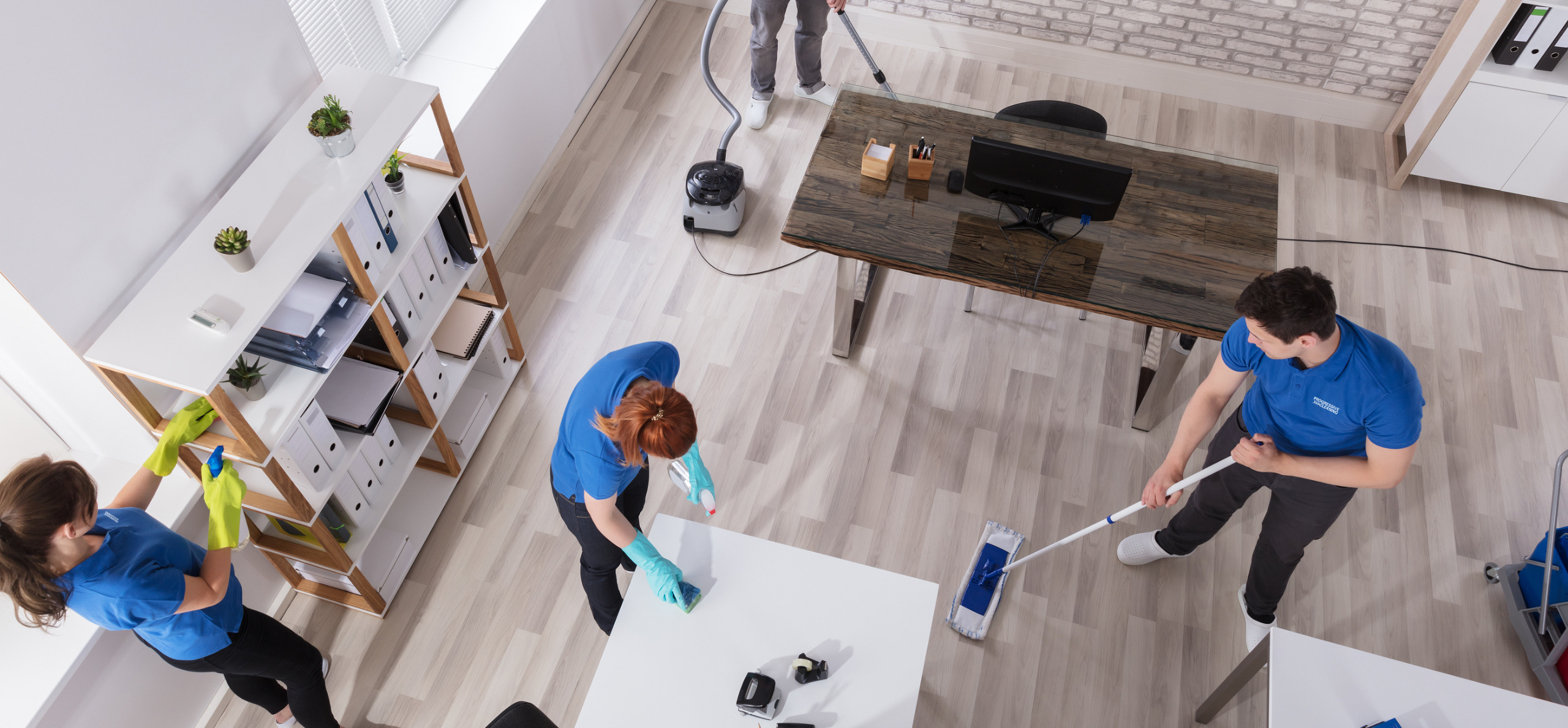 Group of janitors cleaning an office with wood floor using commercial cleaning equipment for a clean and healthy workplace