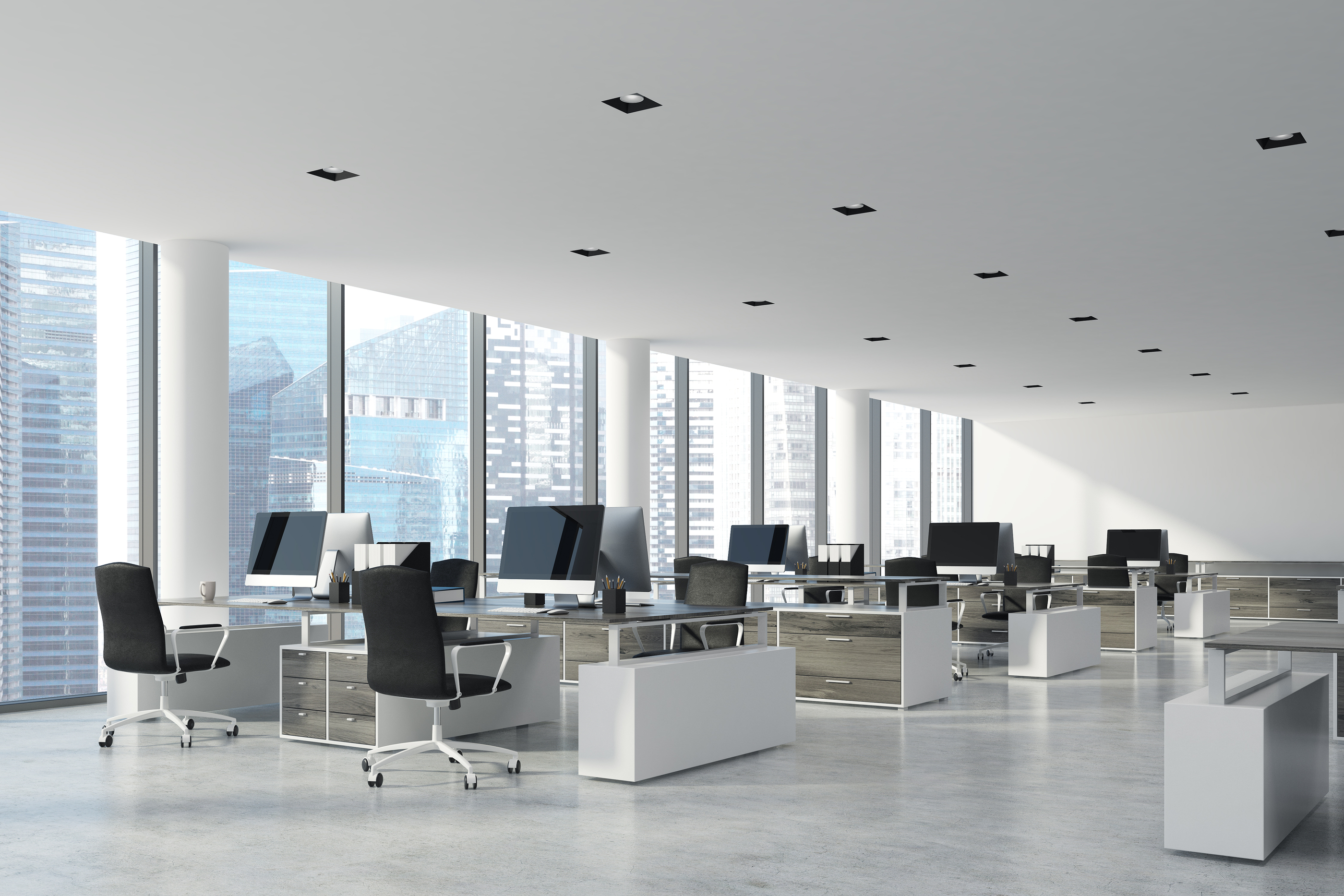 Workplace in an open office with white ceilings and walls and concrete floor