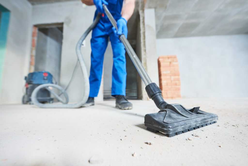 commercial cleaner doing post construction cleaning with vacuum cleaner and lots of dusts