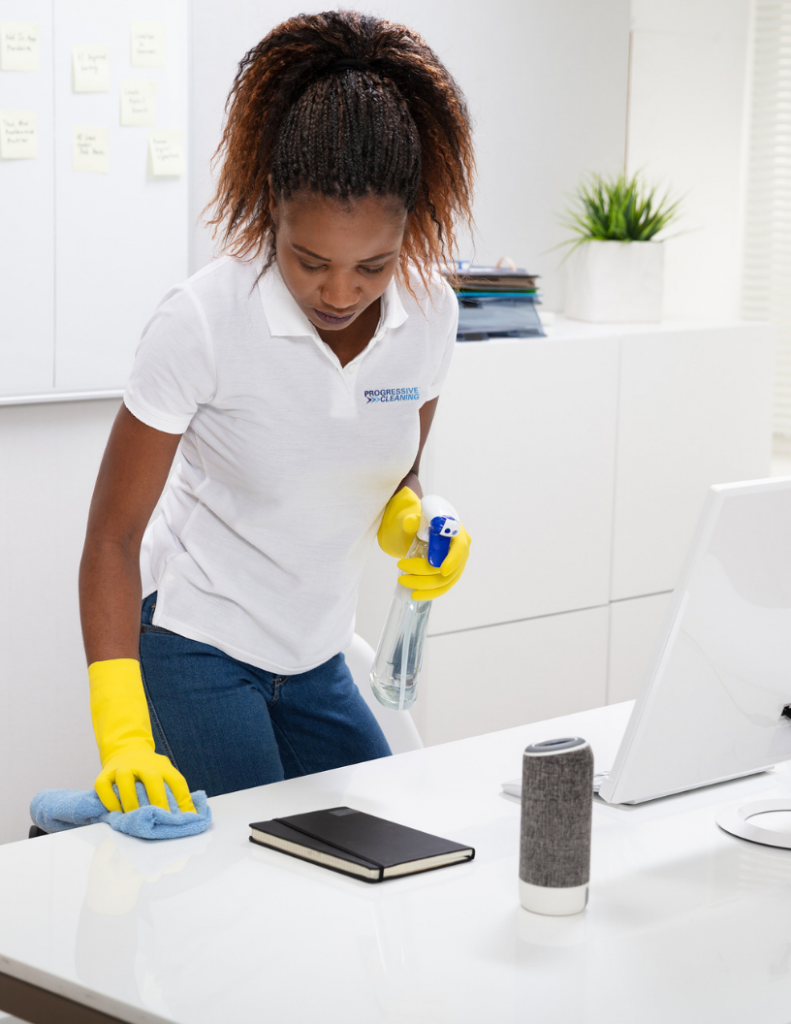 Female commercial janitor with white company shirt cleaning an office for a clean and healthy workplace