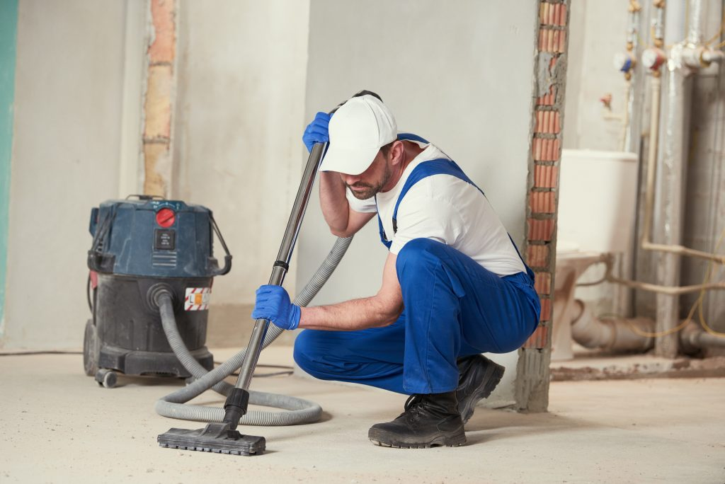 commercial cleaner post construction cleaning with vacuum a white hat and construction boots