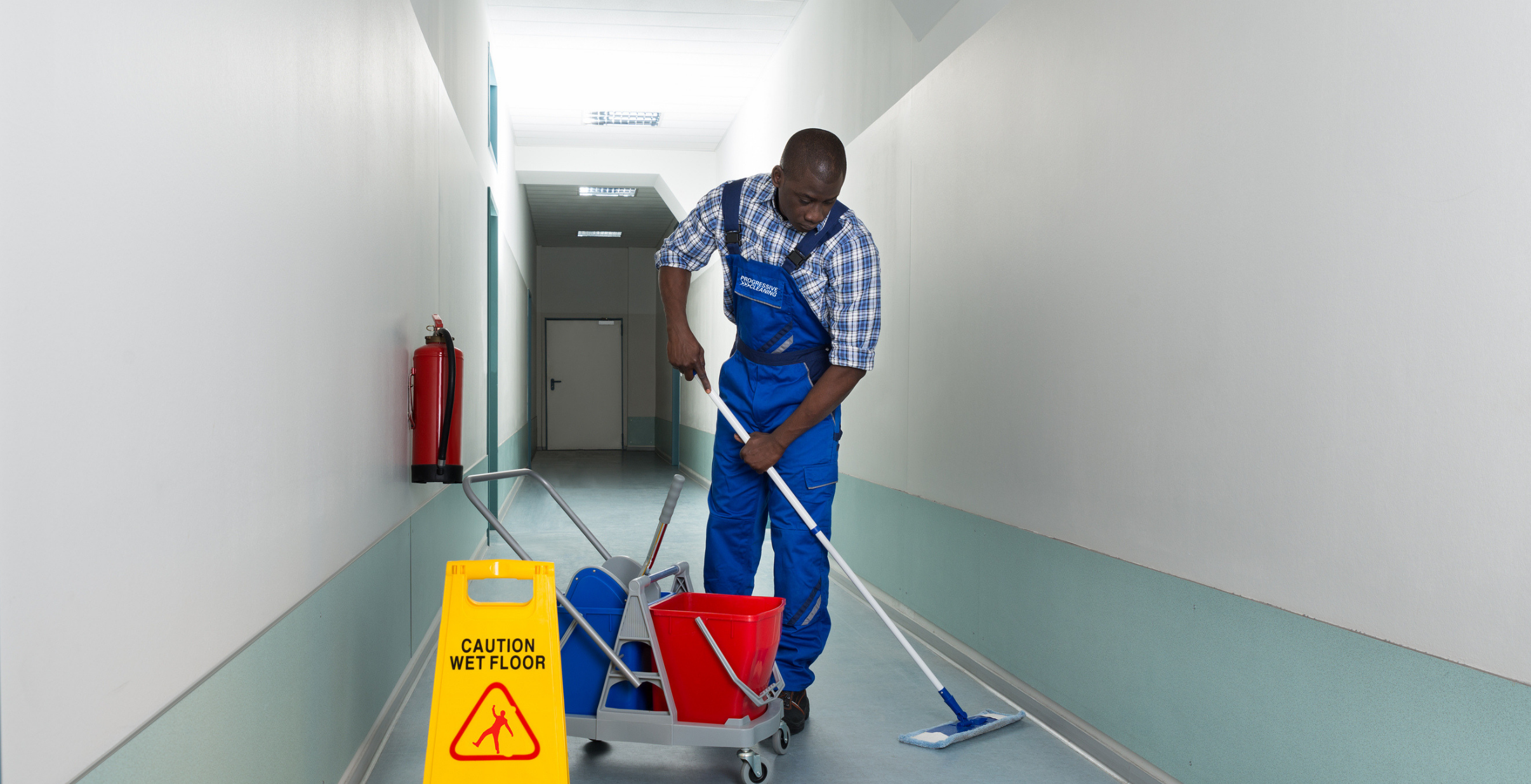 ecosensitive Male commercial cleaner mopping vinyl floor with microfiber mop in blue uniform