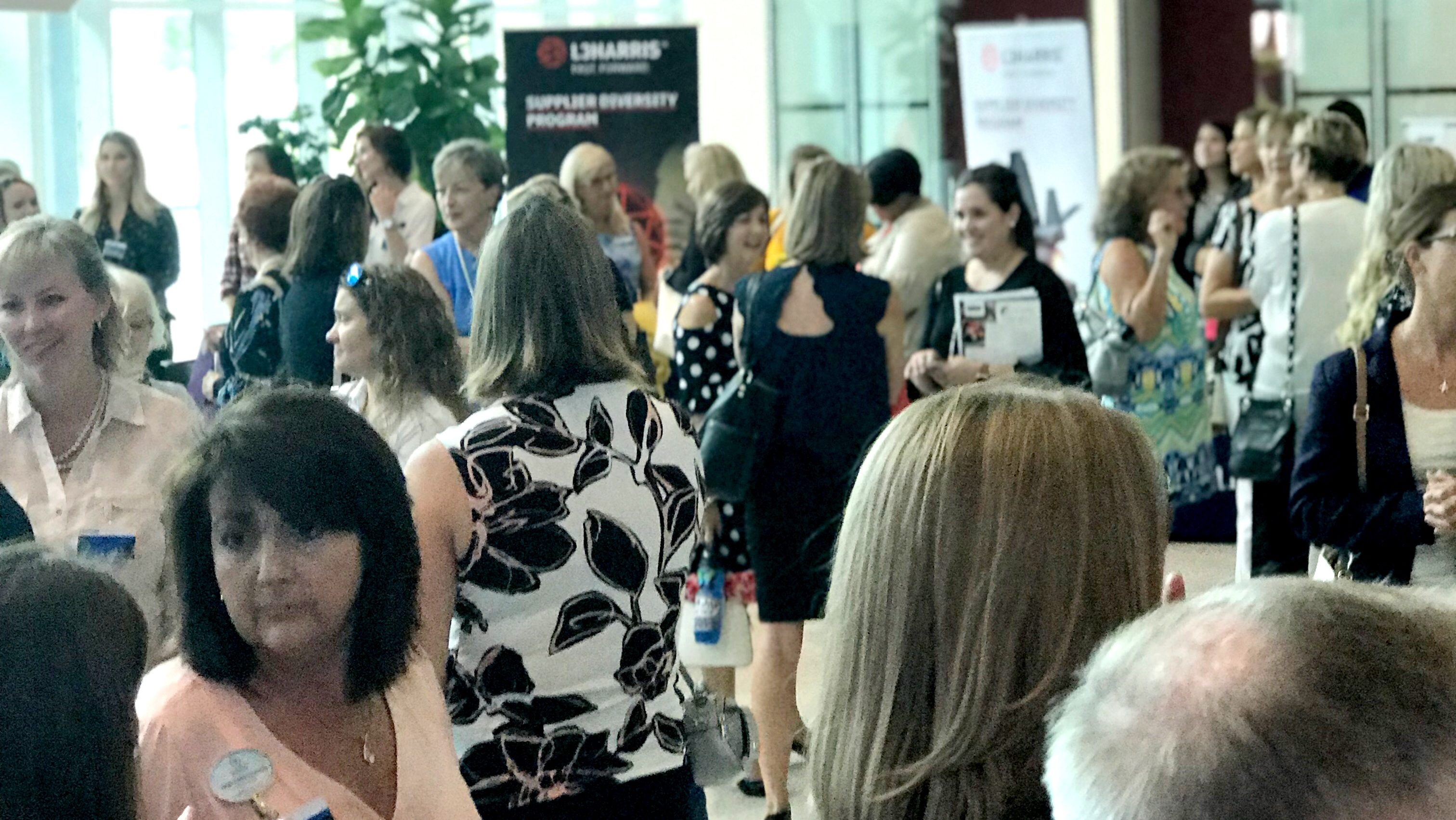Attendees of weVENTURE IMPACT Summit gather in the lobby of L3Harris in Palm Bay
